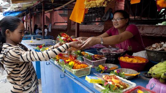 Om te offeren heeft Sanu (12) wat spullen nodig. Bij veel tempels staan kraampjes met bloemen, wierook en kaarsen.