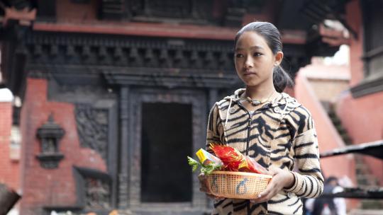Sanu loopt met bloemen, wierook en kaarsjes naar het altaar.