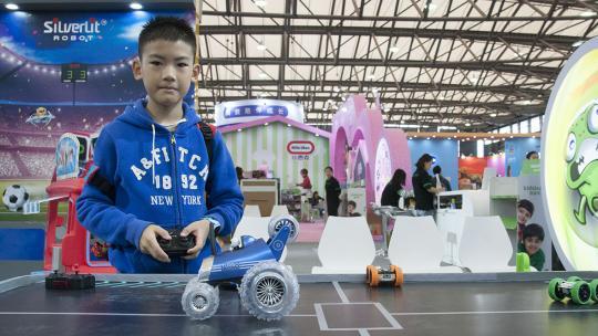 De Chinese Ethan probeert speelgoed uit op de speelgoedbeurs in Shanghai