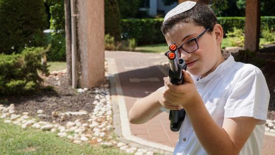 Eitan uit El Aviv is opgegroeid met echte wapens, maar hij speelt met nep-pistolen en nep-mitrailleurs.