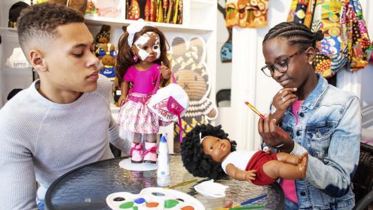 Eliyha en Shué kijken naar bruine poppen met een getekende huidaandoening.