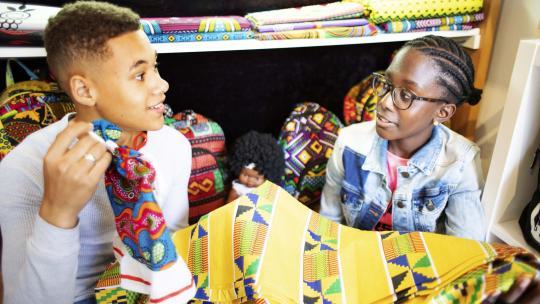 Shué en Eliyha zoeken een stuk stof uit voor nieuwe kleertjes voor een pop.