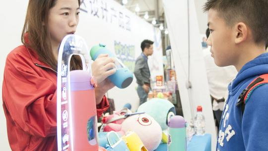 Ethan uit China probeert een heel speciale drinkwaterfles uit op de speelgoedbeurs in Shanghai.