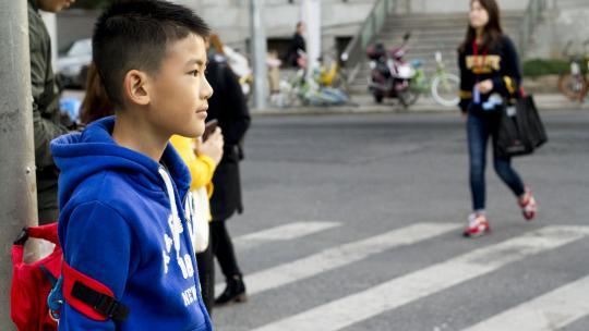 Ethan uit Shanghai wacht op het zebrapad om over te steken.