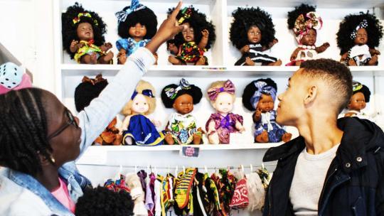 De poppen in deze winkel hebben allemaal verschillende huidskleuren en kapsels. Shué wijst aan welke pop ze voor Kerst heeft gevraagd.
