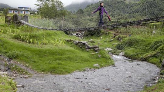 Sudha uit Nepal loopt over een smalle loopbrug over een snelstromend beekje dat uit de bergen komt.