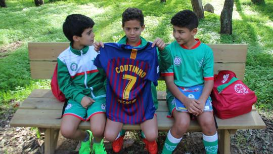 Ali laat z'n shirt van de Braziliaanse voetballer Coutinho zien.