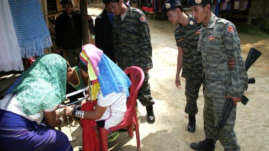 In het dorp van de Karen houden Thaise soldaten alles in de gaten.
