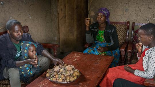 Irere eet met haar familie uit een grote schaal.