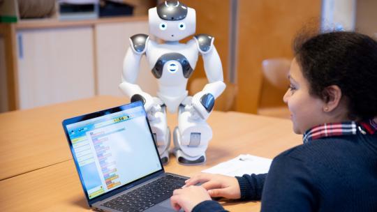 Op de laptop laat Houda zien hoe ze robot Nao programmeert.