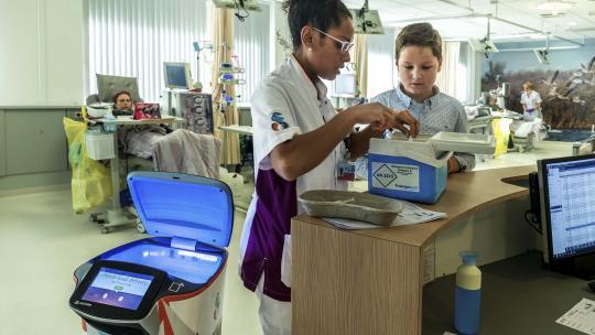 Een verpleegkundige zet buisjes bloed in de robot.