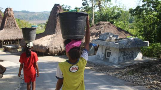 Jenny (links) en Namo halen water: een typisch vrouwenklusje op hun Indonesische eiland.