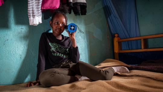 Simantoi uit Kenia luistert naar Serian FM via haar draagbare radio.