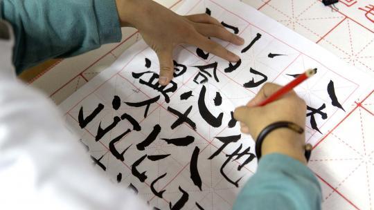 Alexandra uit Shanghai leert kalligrafie van haar moeder.