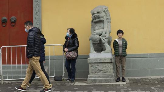 Usher staat bij een beeld voor een tempel in Shanghai.