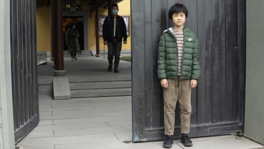 Usher uit Shanghai staat bij een boeddhistische tempel.