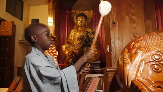 Stephana (12) slaat het ritme op een houten goudvis, terwijl de andere kinderen Chinese liedjes zingen.