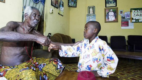 Samuel groet Chief Dozen Ogbariemu (91), de oudste man van het dorp.