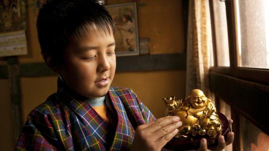 Sherab aait over de buik van de lachende Boeddha; dat brengt geluk