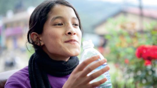 Sudha uit Nepal drinkt water uit een plastic fles.