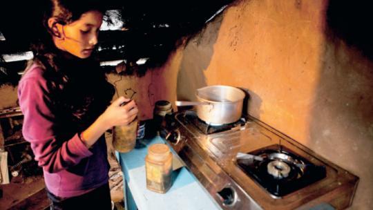 Sudha uit Nepal zet thee in de keuken van haar huis.