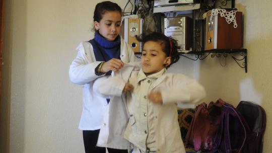 Wiam helpt haar zusje met het schooluniform.