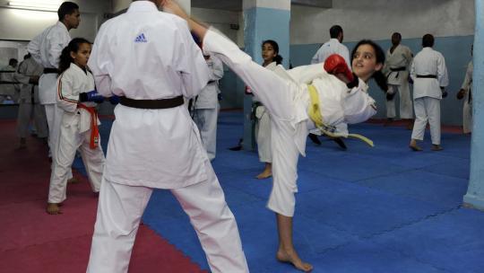 Houda uit Marokko traint serieus tijdens de karate les.
