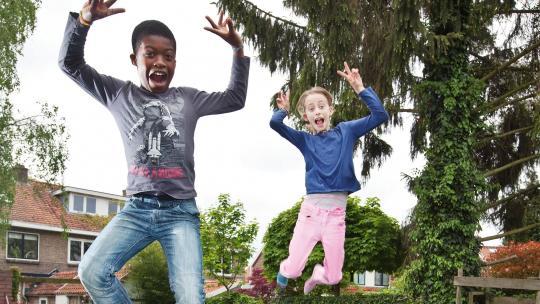 Kiki en Marillio spelen op een trampoline in de tuin.