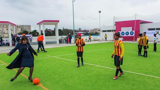 Tijdens een bezoek aan Marokko doet minister Ploumen de aftrap voor een voetbalwedstrijd tussen meidenteams.