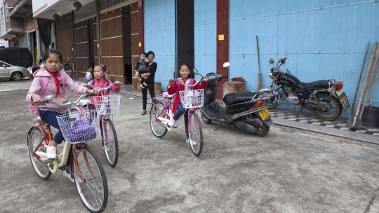 Oma zwaait Xin Ya uit. Ze fietst zelf naar school.
