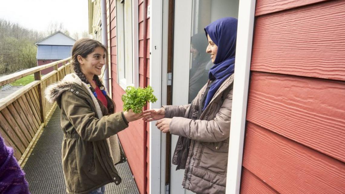 Buurvrouw Huda krijgt peterselie uit de moestuin op het azc.