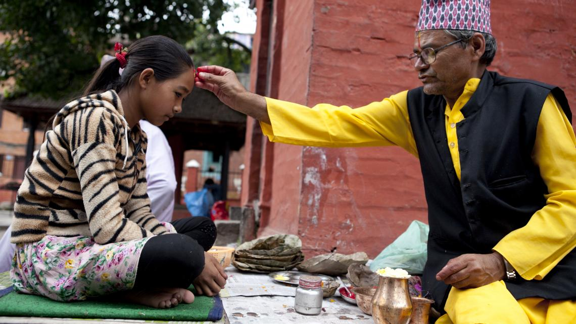 De pandit maakt een bindi op het voorhoofd van Sanu (12) uit Nepal.
