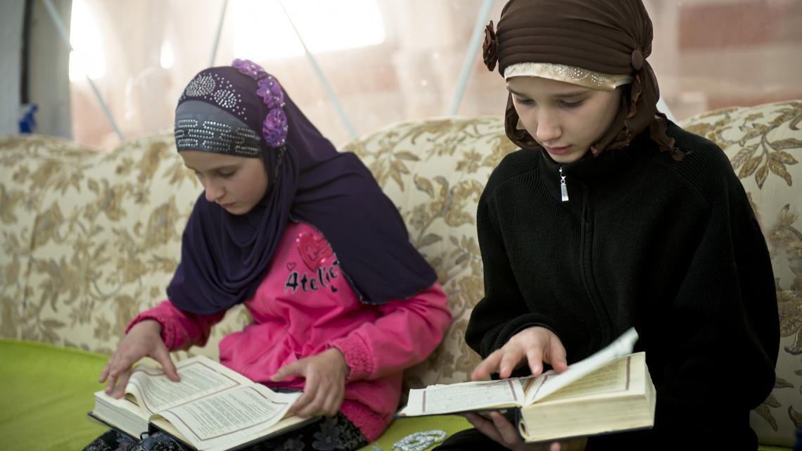 Džejla (12) en haar nichtje lezen uit de Koran.