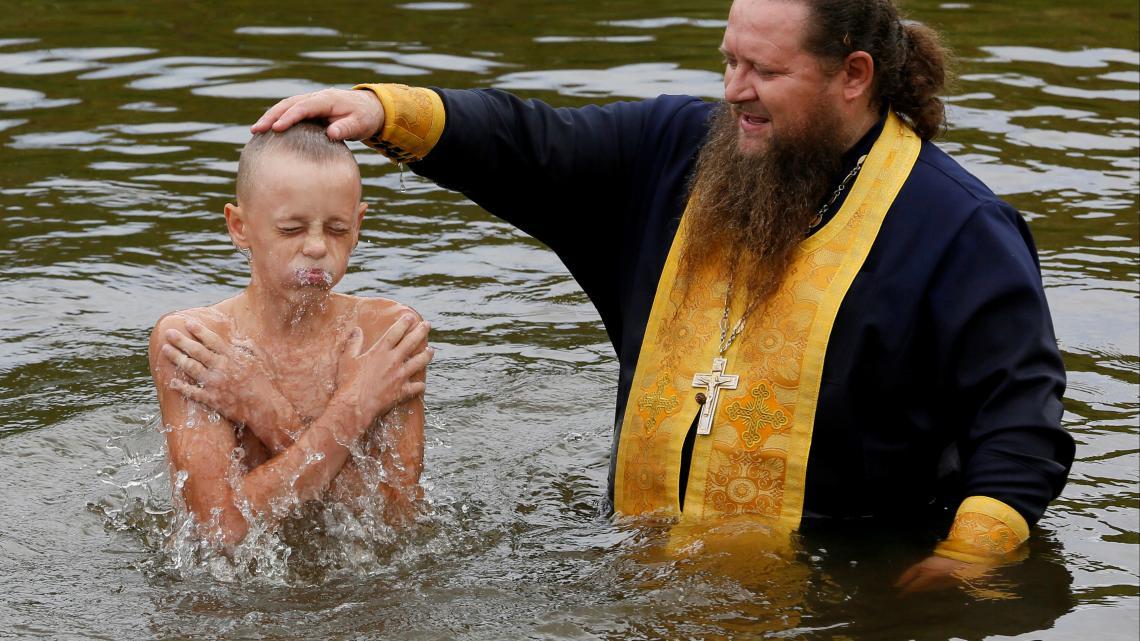 Een orthodoxe priester in Rusland doopt een jongen.