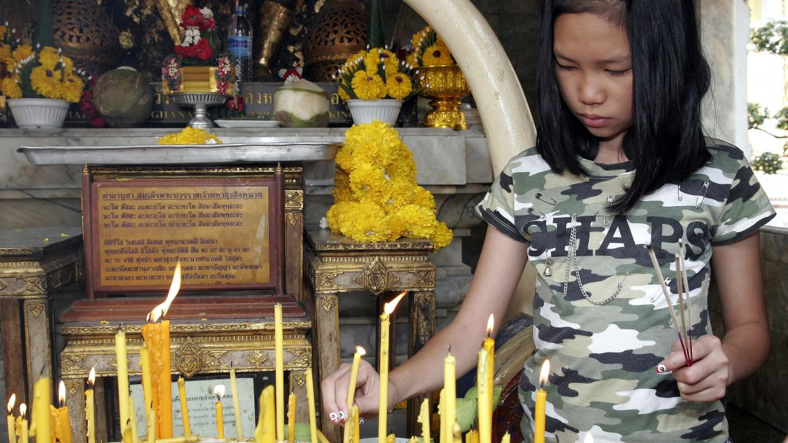 Milk (11) offert kaarsen en brandt wierook in een boeddhistische tempel in Bangkok.