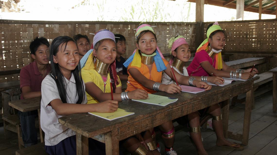 De meisjes zonder de ringen dragen het officiële Thaise schooluniform.