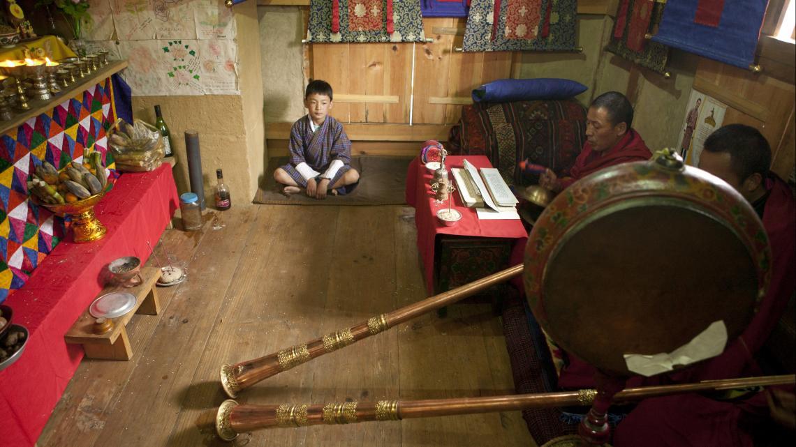 Sonam zit muisstil bij de monniken die in de huistempel hun trompetten laten schallen.