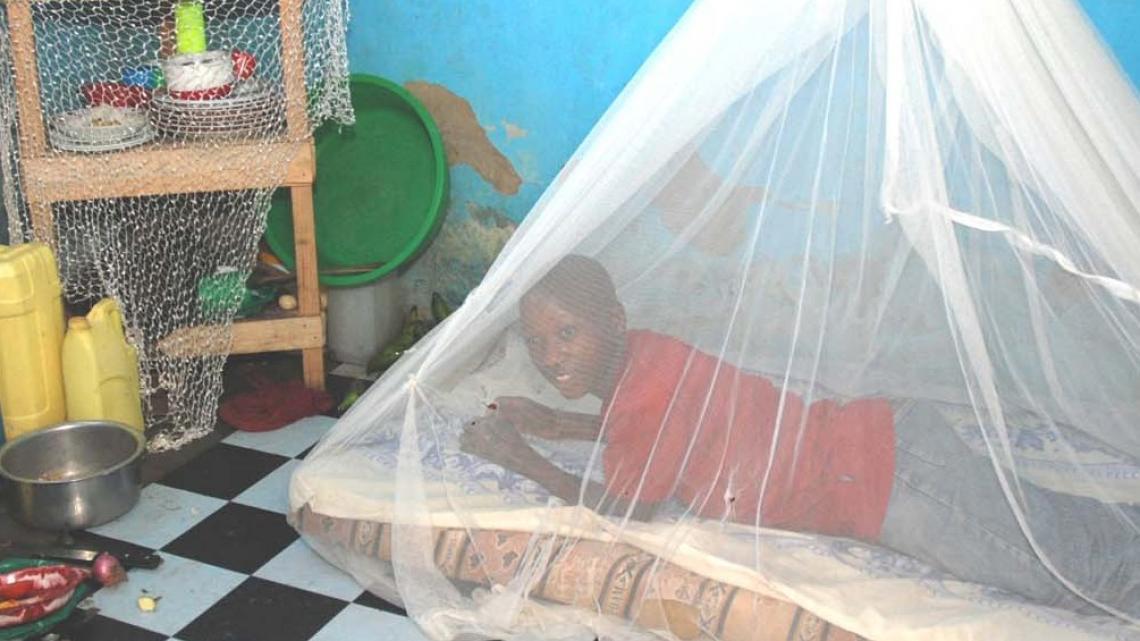 Arnold uit Kampala slaapt onder een klamboe zodat hij geen malaria krijgt.