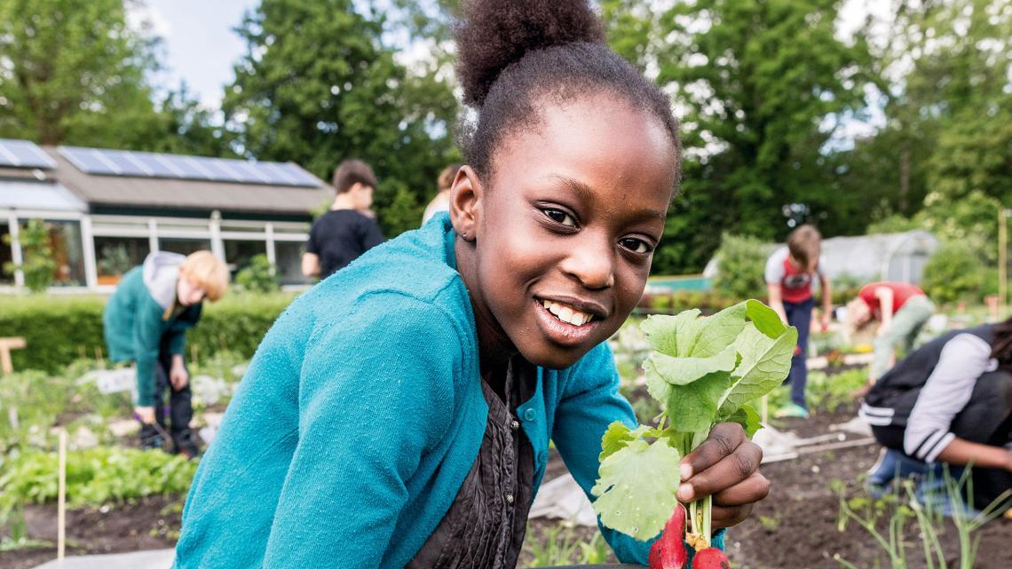 Avelange (10) uit Amsterdam oogst radijsjes in haar schooltuin.