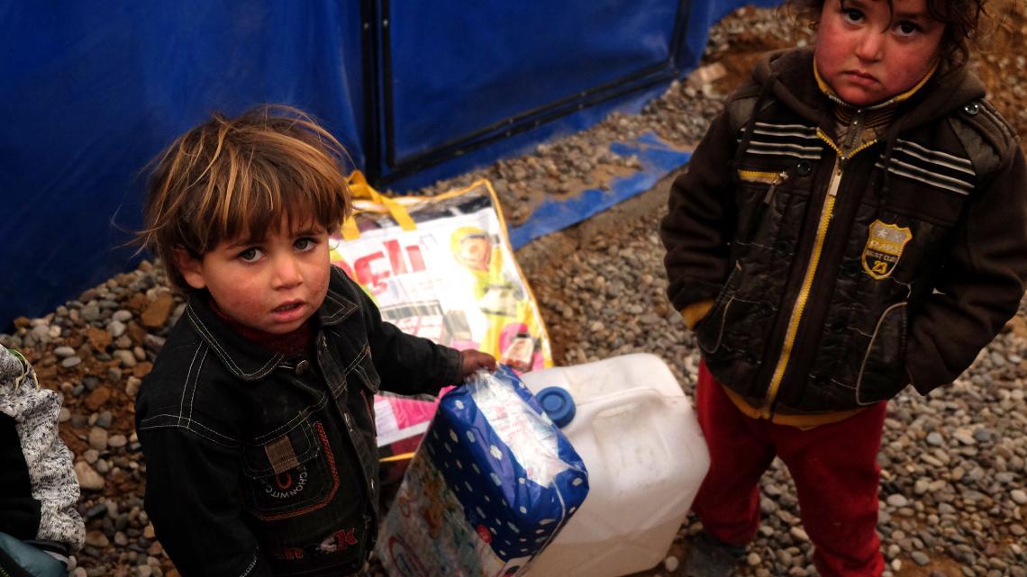 Hulpverleners delen olie en dekens uit tegen de kou in het vluchtelingenkamp