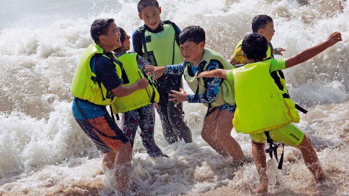 Het clubterrein van Jonathans scoutingclub ligt aan het strand en de scouts spelen graag in de golven.
