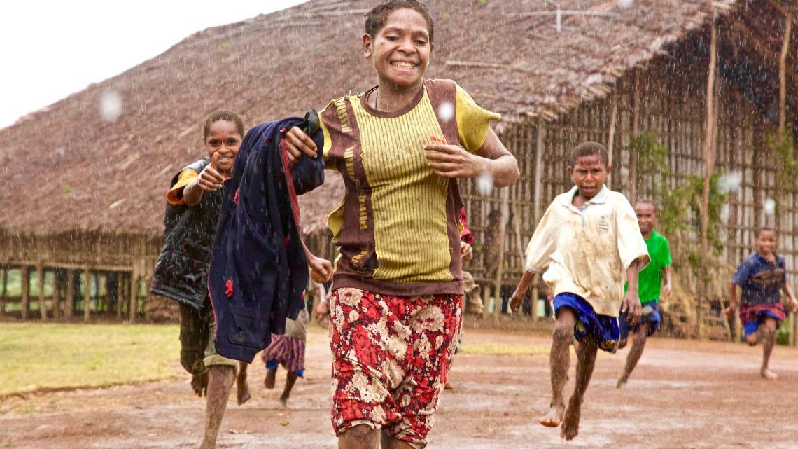 Kinderen rennen in de regen