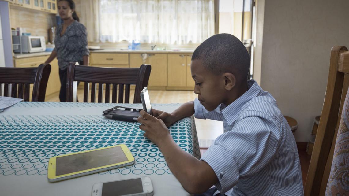 Bruke met zijn telefoon aan de keukentafel