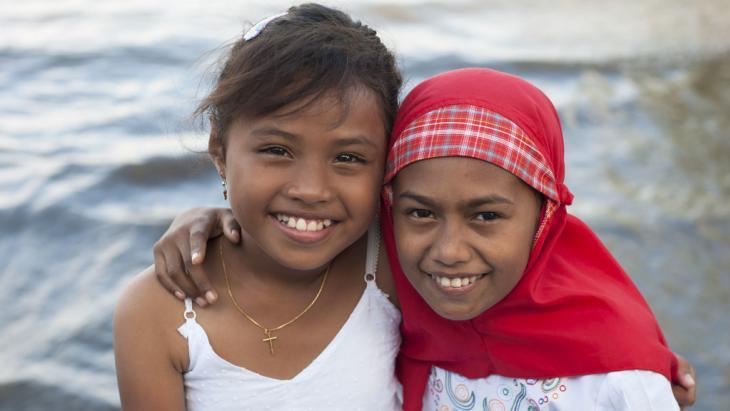 Twee vriendinnen van Ambon omhelzen elkaar.
