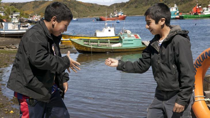 """Claudio en Miguel spelen """"Steen-papier-schaar"""" op het dek van een vissersboot."""
