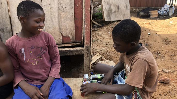 Comfort uit Ghana speelt met zelfgemaakte auto's van gevonden melkblikjes.