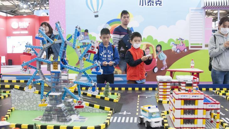 Ethan probeert nieuw speelgoed uit op de beurs in Shanghai.