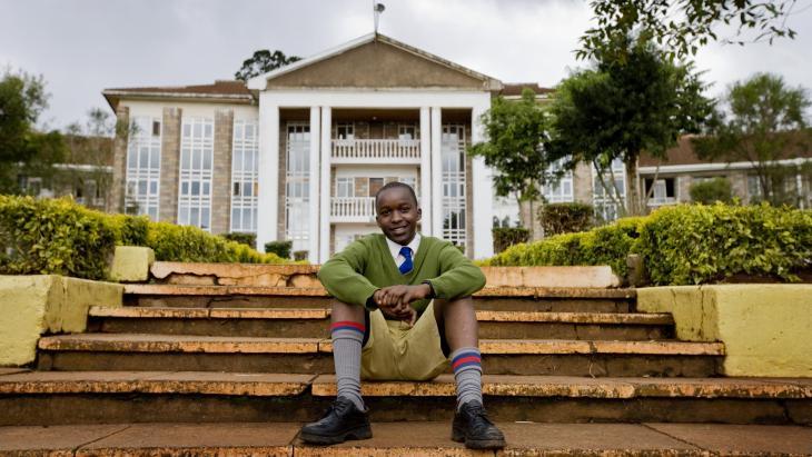 Een leerling poseert voor zijn school in Kenia.