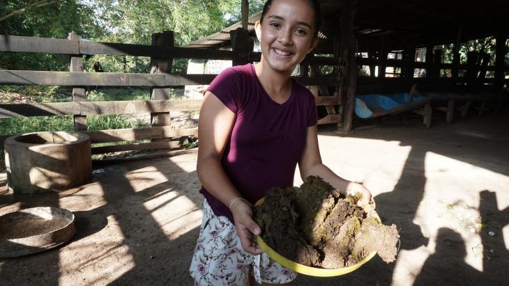 Niky raapt de koeienpoep met haar handen op.