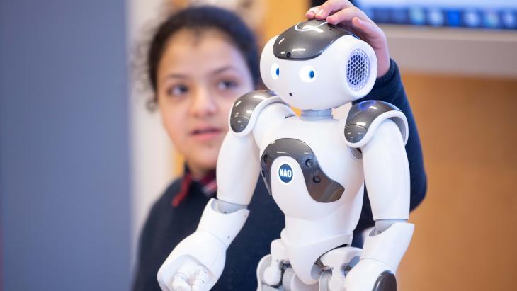 Als Houda op het hoofd van de robot drukt, zegt hij iets.
